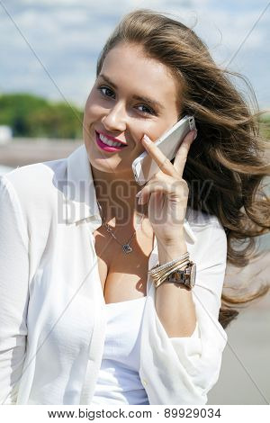 Happy beautiful girl calling by phone in a summer street