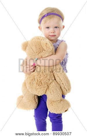 An adorable 2-year-old contentedly hugging her big tan Teddy bear.  On a white background.
