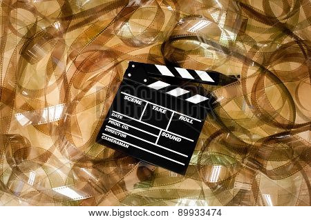 Clapper Board On 35Mm Unrolled Movie Filmstrip Blank Frames Carpet Background