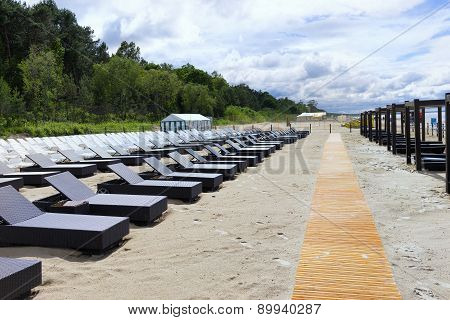 Rows Of Chairs For Sunbathing On The Sandy Beach After Rain