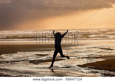 Girl at sunset jumps into water.