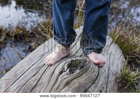 On the log barefooted.