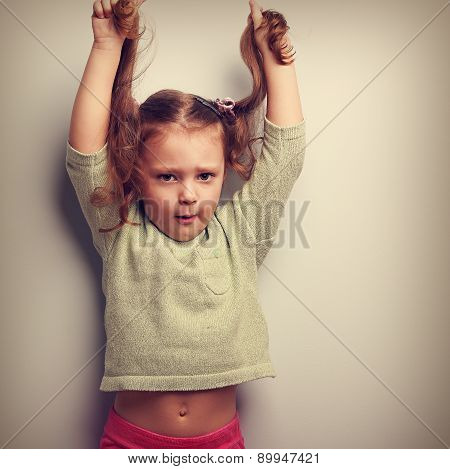 Active Unhappy Emotion Kid Girl Pulling Her Long Hair Up. Vintage Portrait