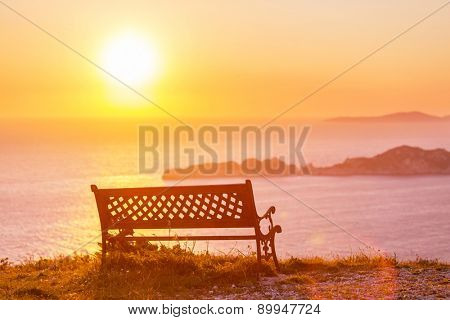 bench on sea coast at sunrice