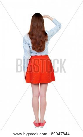 back view of standing young beautiful  woman.  girl  watching. Rear view people collection.  backside view of person. . The girl with long legs looking forward shielding his eyes from the sun.