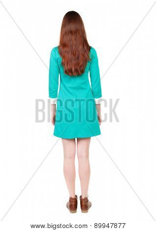 back view of standing young beautiful  woman. backside view of person.  Isolated over white background. The girl in a modest blue dress stands. girl in short dress standing with her hands at his sides