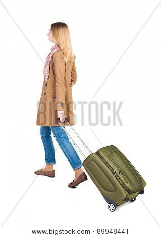 back view of walking  woman  with suitcase. beautiful girl in motion.  backside view of person.  Rear view people collection.  traveling teen girl. Fashionable girl rolls a suitcase.