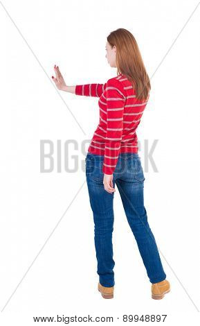 back view of woman. Young woman presses down on something.  backside view of person. she holds his hand open, palm forward. Girl in a striped red sweater showing stopping hand gesture.