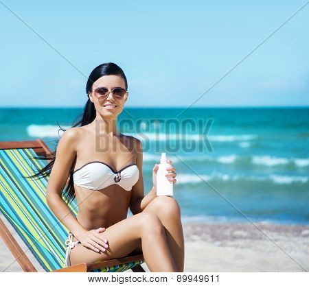 Young, beautiful, sporty and sexy woman using the suntan cream on the beach