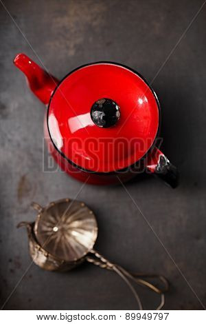 vintage red teapot and mesh strainers on dark metal table