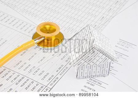 Yellow And Gold Stethoscope With House Place On Balance Sheet