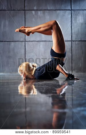 Young woman modern dancer stretching legs upside down. On stone wall background.