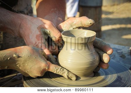 potter helps the child to make a vase from clay