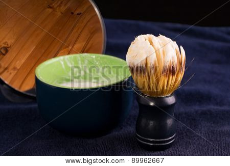 Shaving brush with foam, soap cup and mirror on dark blue towel