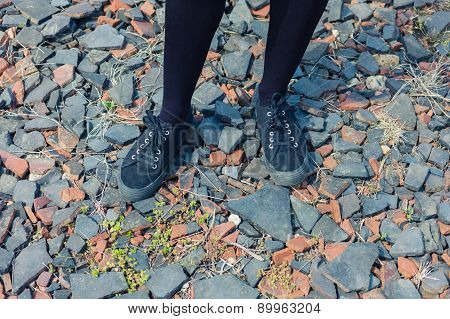 Feet And Legs Of Young Woman Standing On Gravel