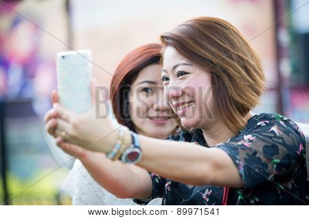 Happy Asian Woman With Friend Taking A Selfie