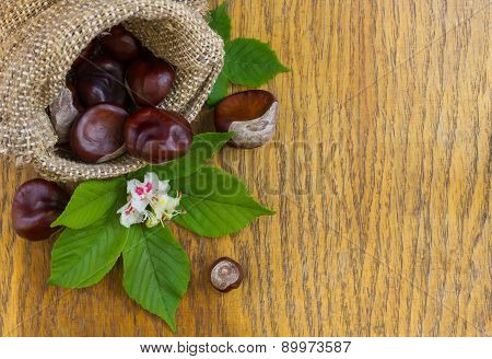 Chestnuts In Burlap On Wood Textured