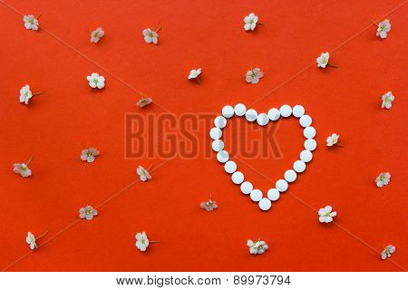 Heart Shape Made Of White Pills With White Flowers Pattern On Orange Background.useful As Background