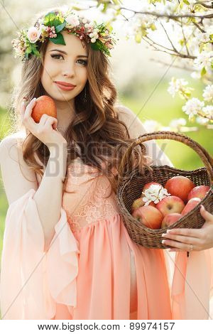 Pregnant woman in the spring garden with a basket of ripe apples.