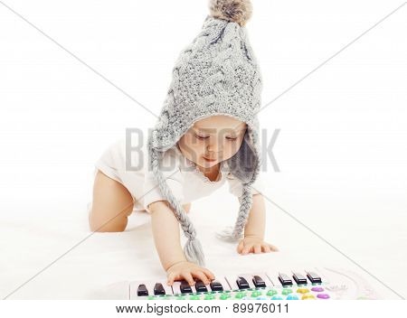Development Child, Baby In Knitted Hat Playing On The Piano