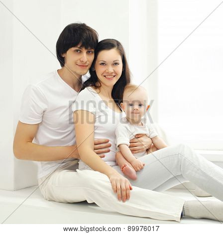 Family Portrait Of Happy Parents And Baby At Home In White Room Near Window