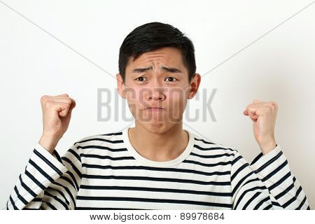 Displeased young Asian man shaking two fists.
