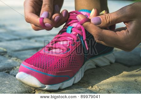Hands Of A Young Woman Lacing Sneakers