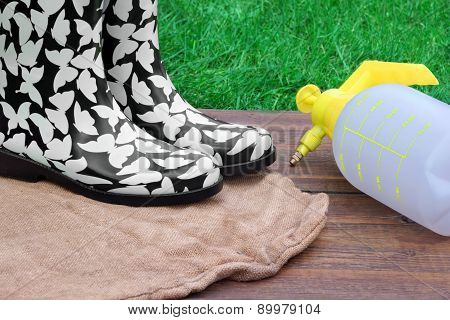 Female Rubber Boots And Watering Can On The Wood Desk