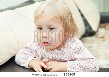 Little Child A Dlond Girl Sitting On Sofa And Looking Through