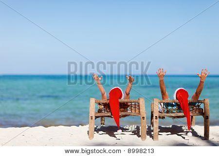 Couple In Santa Hats On Tropical Beach