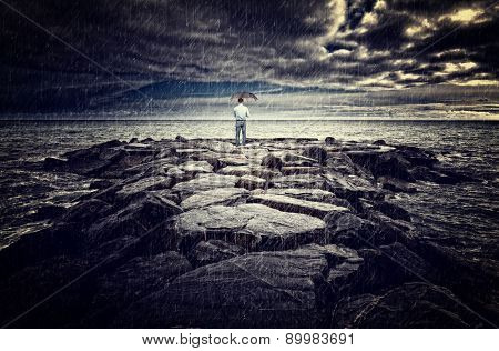 man with umbrella on sea rock bad weather