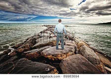 standing photographer on sea rock reef