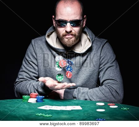 poker player with sunglasses play with chips