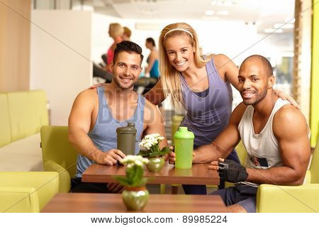 Athletic young people in gym bar, smiling, drinking refreshment, looking at camera.