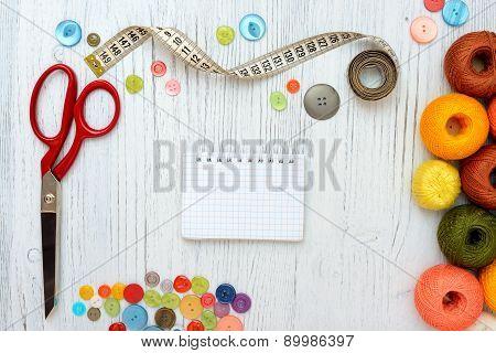 Copyspace frame with sewing tools and accesories on white wooden background