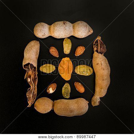 Tamarind, Raisins And Almond Composition On Black Background