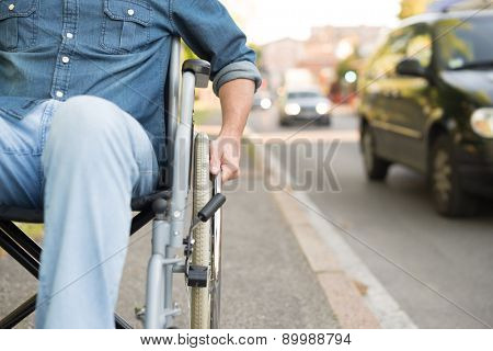 Detail of a man using a wheelchair in an urban street