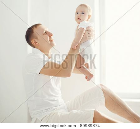 Happy Father Holding On Hands His Baby At Home In White Room Near Window