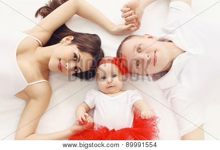 Portrait Of Happy Family Together Lying On The Bed At Home, Top View