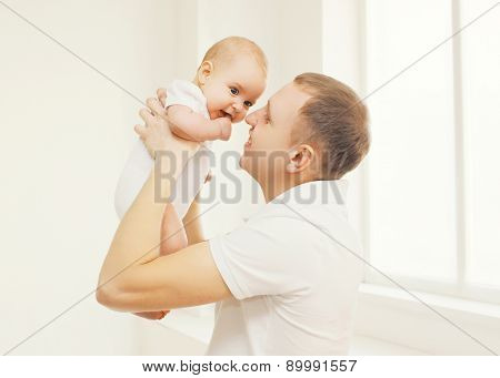 Portrait Of Happy Father Holding On Hands His Baby At Home