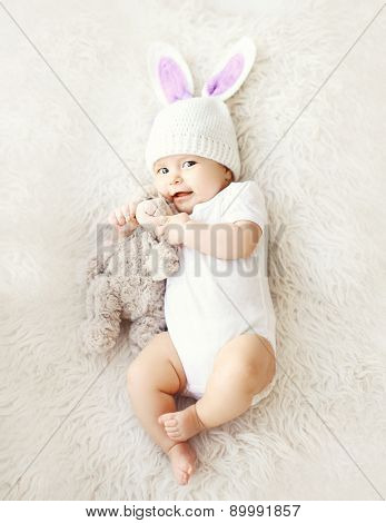 Soft Photo Of Sweet Cute Baby In Knitted Hat With A Rabbit Ears And Teddy Bear Lying On The Bed, Top