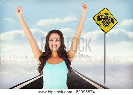 Casual brunette cheering at camera against road leading to city