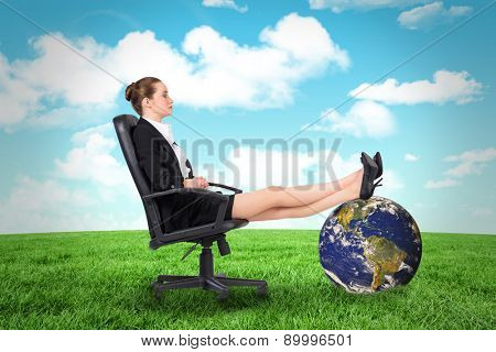Businesswoman sitting on swivel chair with feet up against field and sky