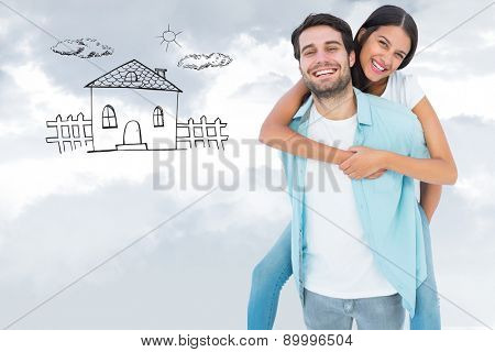 Happy casual man giving pretty girlfriend piggy back against grey cloudy sky