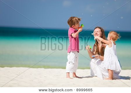 Mother And Kids Having Fun On Beach