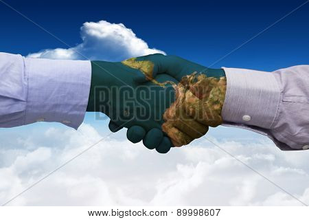 Hand shake in front of wires against bright blue sky with clouds