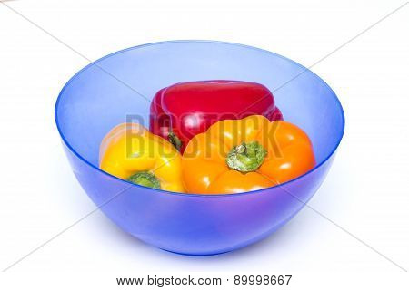 Three whole peppers of different colors in blue bowl for food