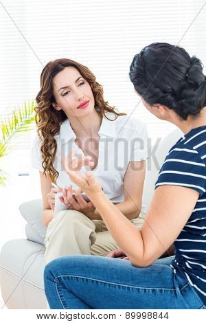 Therapist listening her patient and taking notes on white background