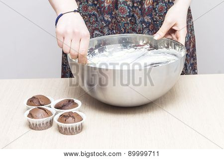 Woman cooking cream for cupcakes