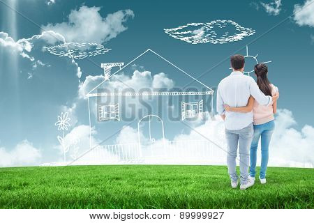 Attractive young couple standing with arms around against blue sky over green field